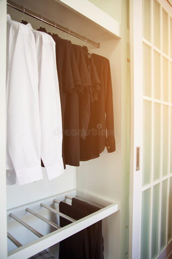 La ropa cuelga en un estante en la ropa de un diseñador tienda, armario moderno con la fila de la ropa que cuelga en guardarropa, fotografía de archivo