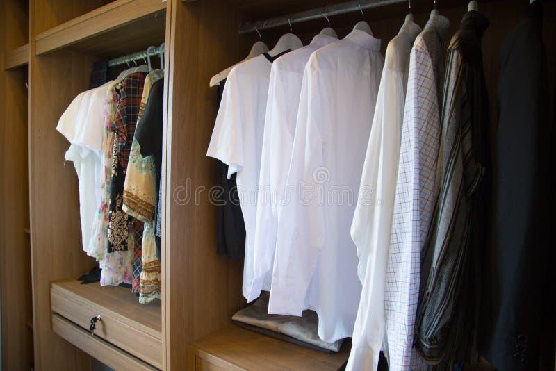 La ropa cuelga en un estante en la ropa de un diseñador tienda, armario moderno con la fila de los paños que cuelgan en guardarro imagen de archivo