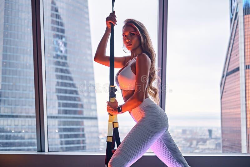 La ropa de deportes que lleva de la muchacha hermosa está presentando con las correas de la ejecución en un apartamento del rasca foto de archivo libre de regalías