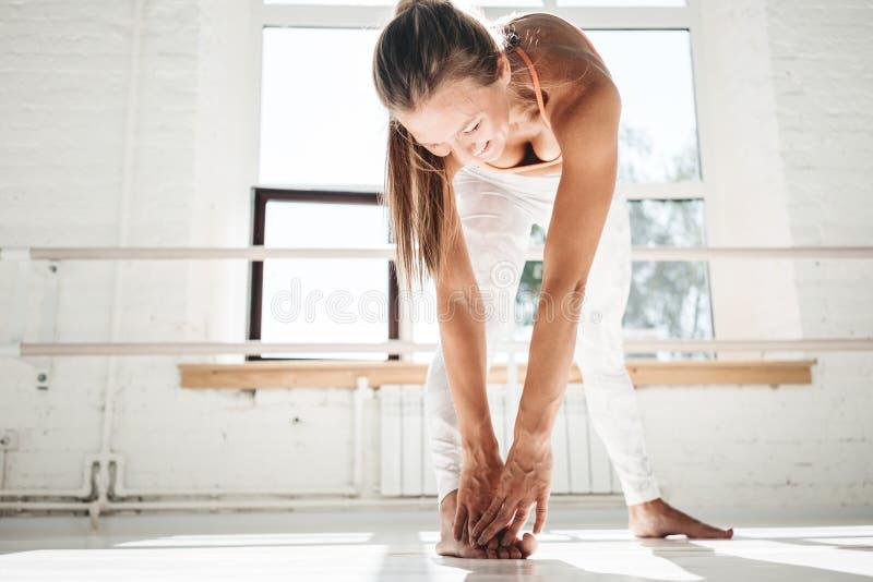 La ropa de deportes que lleva de la mujer feliz del ajuste que hace estirar ejercita en clase del deporte interior de las piernas imagenes de archivo