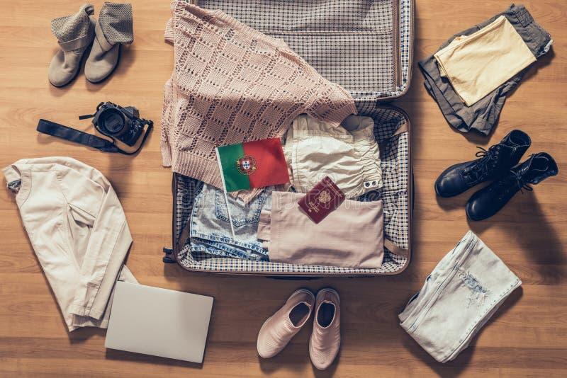 La ropa de la mujer, ordenador portátil, cámara, pasaporte ruso y bandera de Portugal mintiendo en el piso de entarimado cerca y  foto de archivo libre de regalías