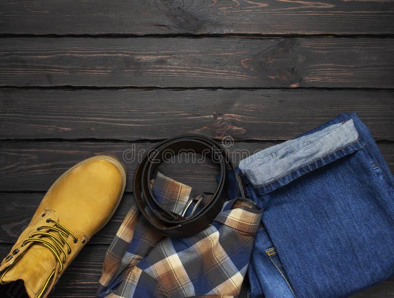 La ropa de sport de los hombres, botas amarillas del trabajo del cuero natural del nubuck, tejanos, camisa a cuadros y correa mar fotos de archivo