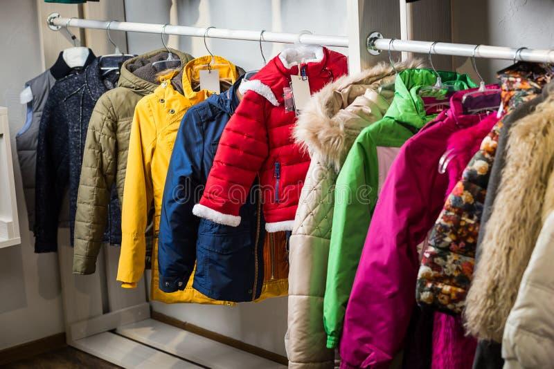 La ropa del bebé cuelga en un estante en una tienda del diseñador foto de archivo