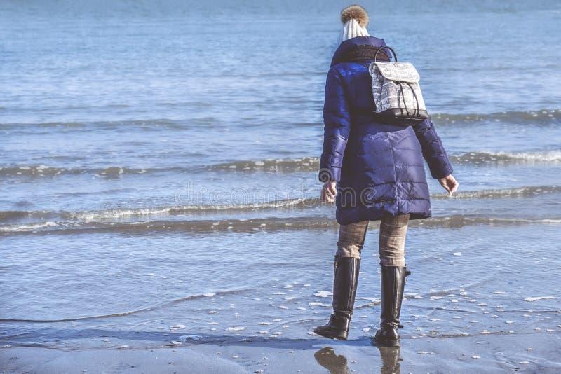 La ropa del invierno de la muchacha que lleva camina en orilla de mar detrás ve con BO fotografía de archivo