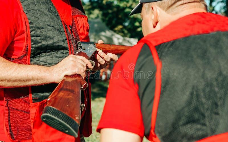 La ropa especial de dos cazadores considera la escopeta fotos de archivo
