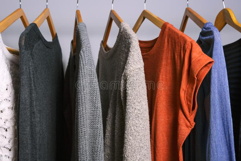La ropa femenina que cuelga en una ropa atormenta en una tienda o clos caseros imagen de archivo libre de regalías