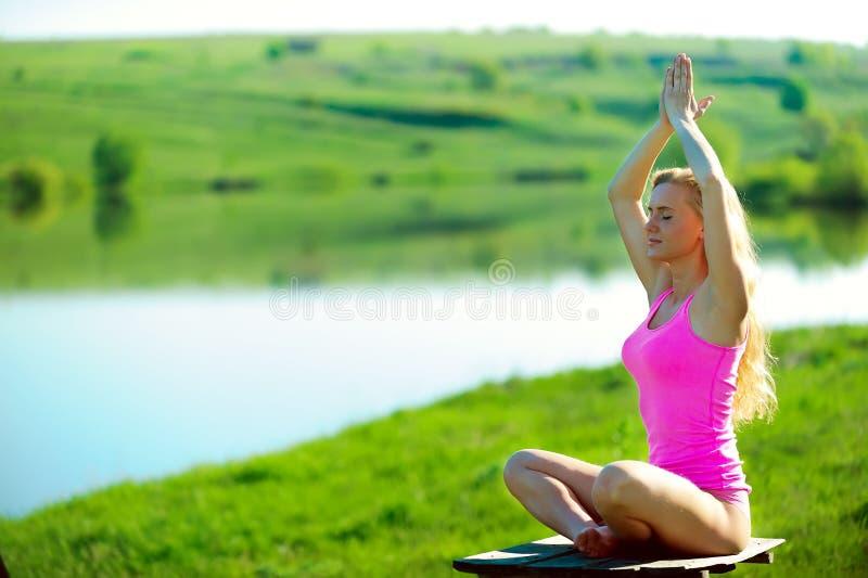 La ropa hermosa de la muchacha del positiveblond en rosa se sienta en el riversi foto de archivo libre de regalías