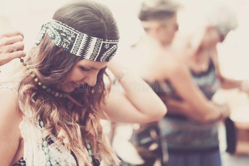 La ropa india del estilo del hippy alegre y la se?ora joven de los accesorios ponen un collar y disfrutan del pasatiempo con los  foto de archivo libre de regalías