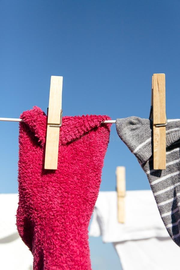 La ropa/los calcetines coloridos colgó hacia fuera para secarse en el sol caliente brillante fotos de archivo
