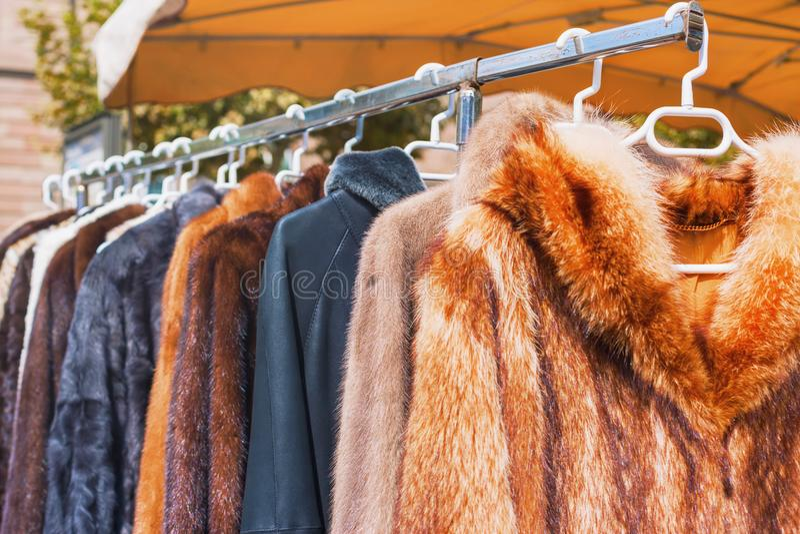 La ropa para la venta para el invierno sazona la ejecución en un estante en el mercado de pulgas al aire libre fotos de archivo libres de regalías