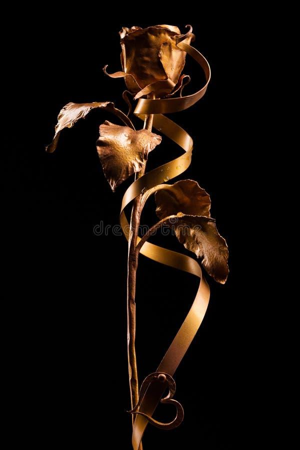 La rosa de oro con un corazón hecho del metal, en fondo negro foto de archivo libre de regalías