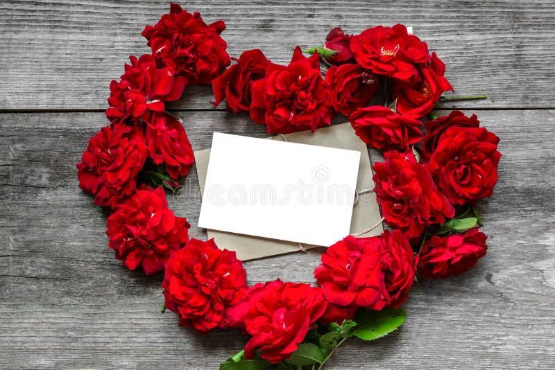 La rosa rossa di forma del cuore fiorisce con la cartolina d'auguri in bianco su fondo di legno rustico fotografia stock