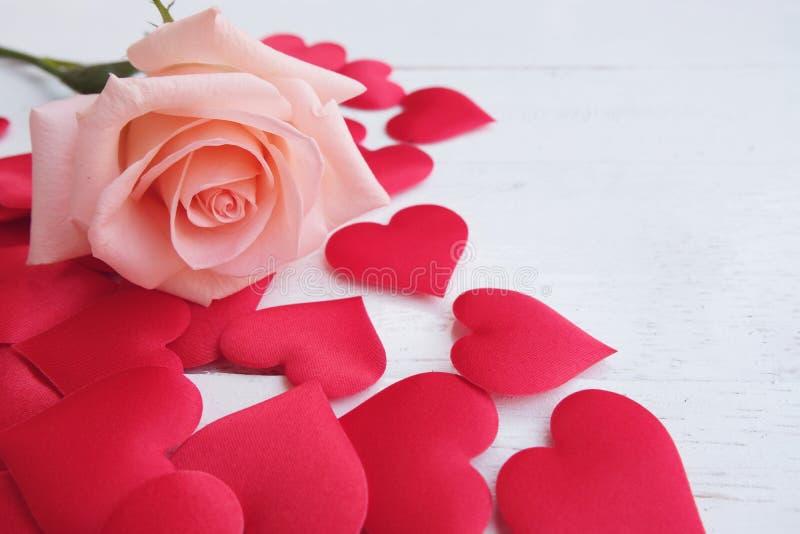 La rose rose-orange de beauté et les coeurs rouges de satin forment sur le plancher en bois Valentine&#x27 ; concept de fond de j photo stock
