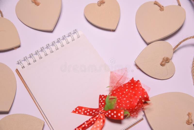 La rose rouge sur le bloc-notes vide pour l'espace de copie et les coeurs en bois forment sur le blackground blanc Fond de jour d photographie stock