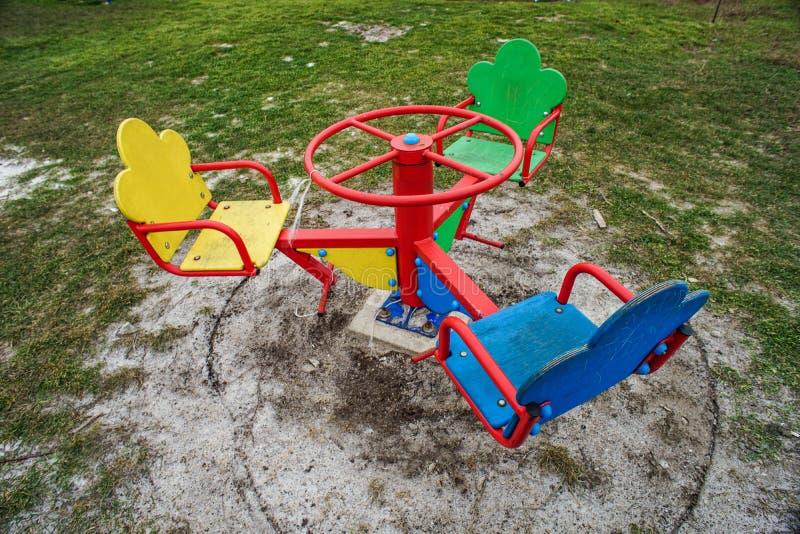 La rotonda dei bambini per tre con i sedili di legno per la seduta nei colori differenti Campo da giuoco vuoto un giorno nuvoloso fotografia stock libera da diritti