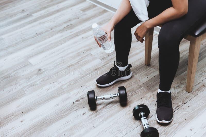 La rotura de la muchacha de la aptitud para el agua potable que se sienta con pesas de gimnasia carga el entrenamiento fotos de archivo