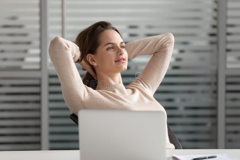 La rotura soñadora tranquila de la toma de la empresaria acabó el trabajo para sentarse en el escritorio fotos de archivo libres de regalías