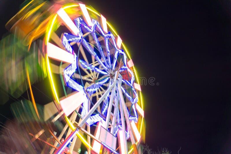 La roue de Ferris tourne la nuit photographie stock