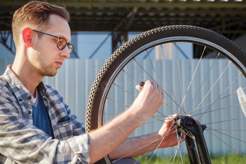 La roue de réparation d'homme de mécanicien de la bicyclette extérieur photos libres de droits