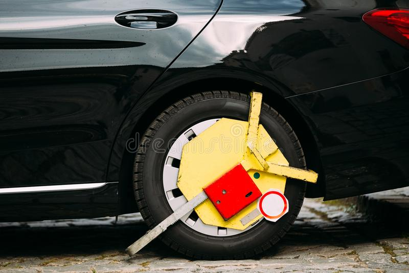 La roue de la voiture a été fermée à clef avec le blocage de roue maintenu par jaune par la police de la circulation photos stock