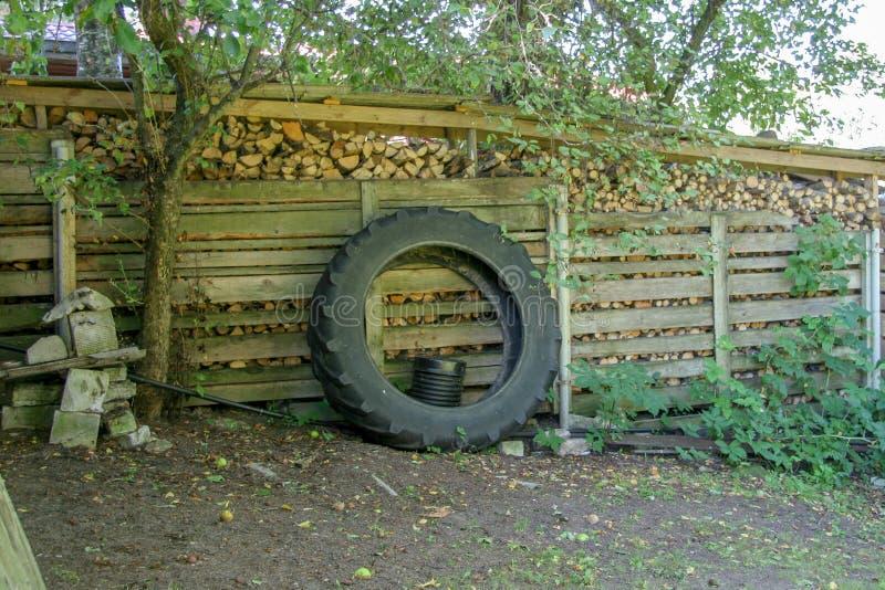 La roue du tracteur se penche contre le tas de bois photo stock