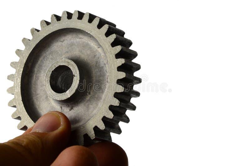 La roue légèrement utilisée de dent d'alliage d'alluminium du pignon droit s'est tenue dans la main gauche sur le fond blanc photos libres de droits