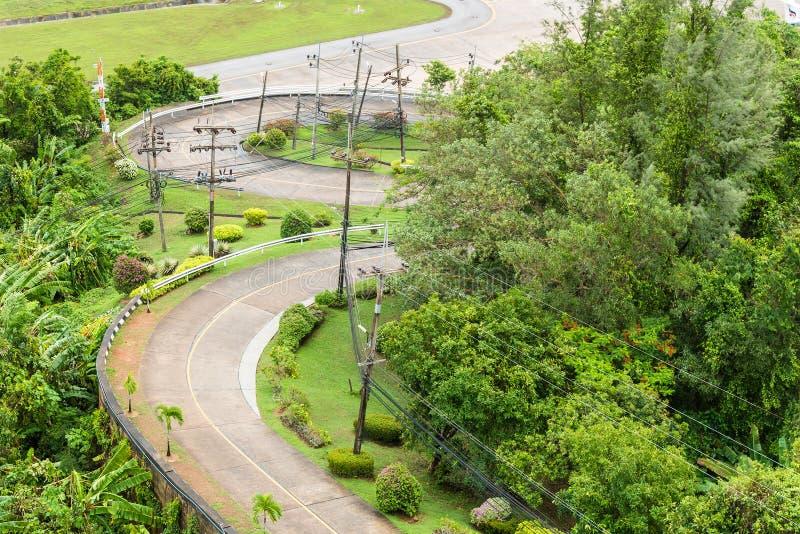 La route bétonnée de 3 courbes est vont vers le bas de la colline avec la forêt images stock