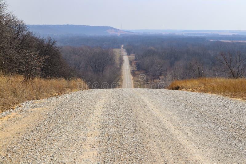 La route continue pour toujours - gravelez la route dans des tronçons d'hiver au-dessus des collines presque à l'horizon flou images libres de droits