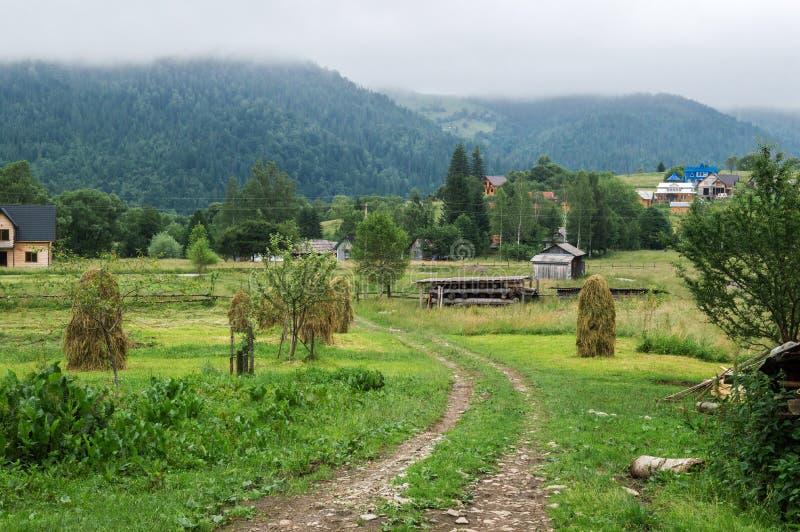 La route de campagne menant après les gerbes de foin à la forêt les montagnes sont envahies avec la forêt conifére, enveloppée da photographie stock