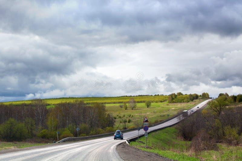 La route entre loin dans la distance, l'horizon, peu de voitures, le champ vert et la forêt, fond nuageux de ciel bleu photo stock