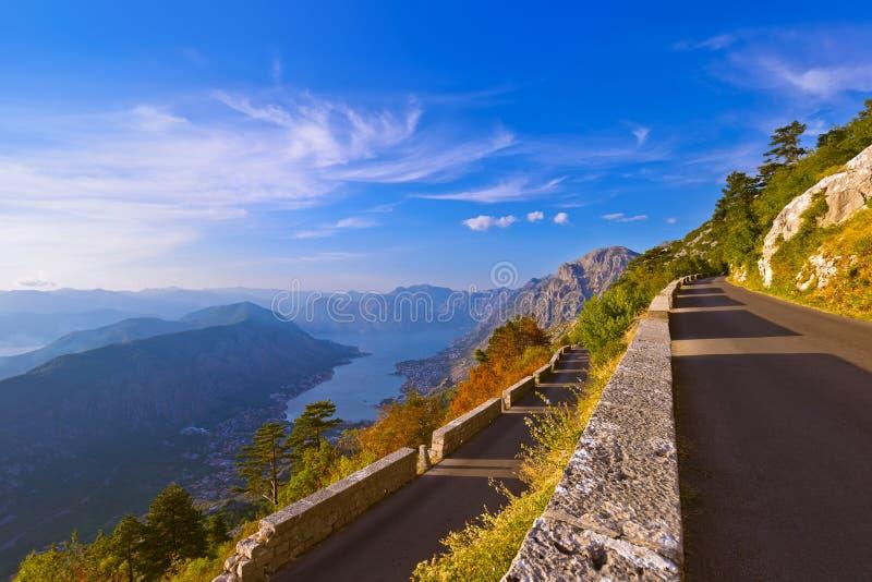 La route et le Kotor de montagnes aboient sur le coucher du soleil - Monténégro photographie stock libre de droits