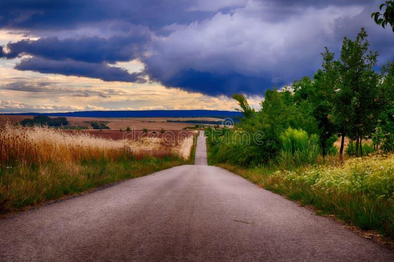 La route goudronnée avec l'horizon le soir sous le congestus foncé de cumulus opacifie images libres de droits