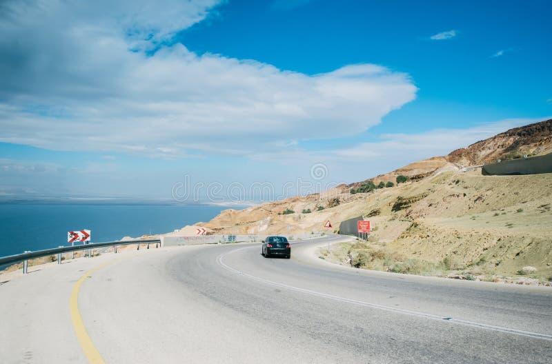 La route goudronnée avec une une voiture le long de la côte de la mer morte dans les montagnes de la Jordanie images libres de droits
