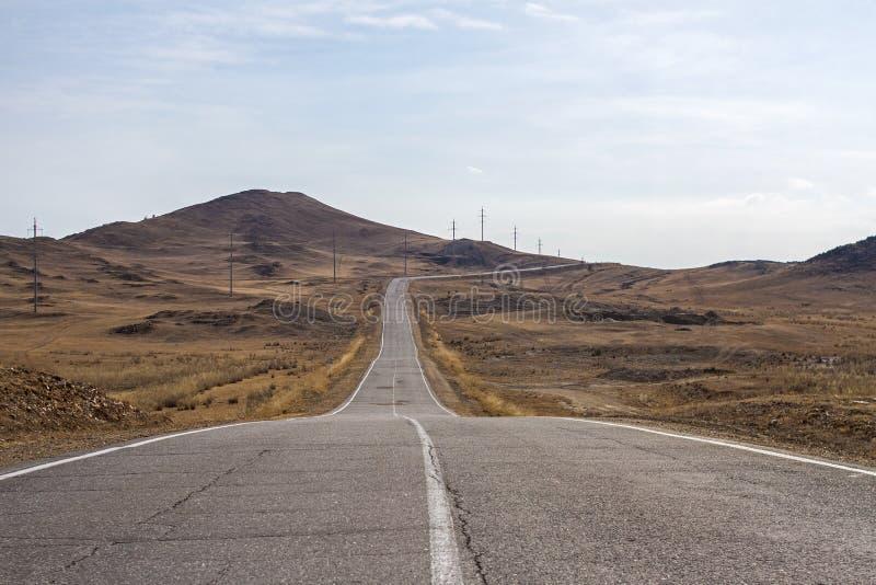 La route goudronnée criquée incurvée vide vers le lac Baïkal est parmi les montagnes avec le ciel clair et l'herbe sèche photos stock