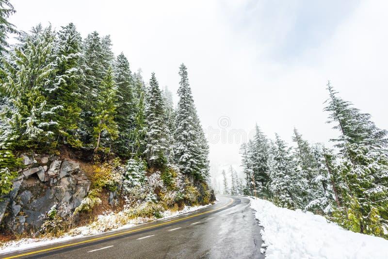 La route vide à la montagne avec la neige a couvert le paysage en hiver images libres de droits