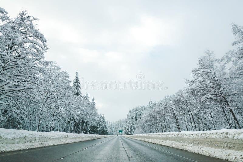 La route vide avec le niveau élevé de neige a couvert le paysage dans la saison d'hiver images libres de droits