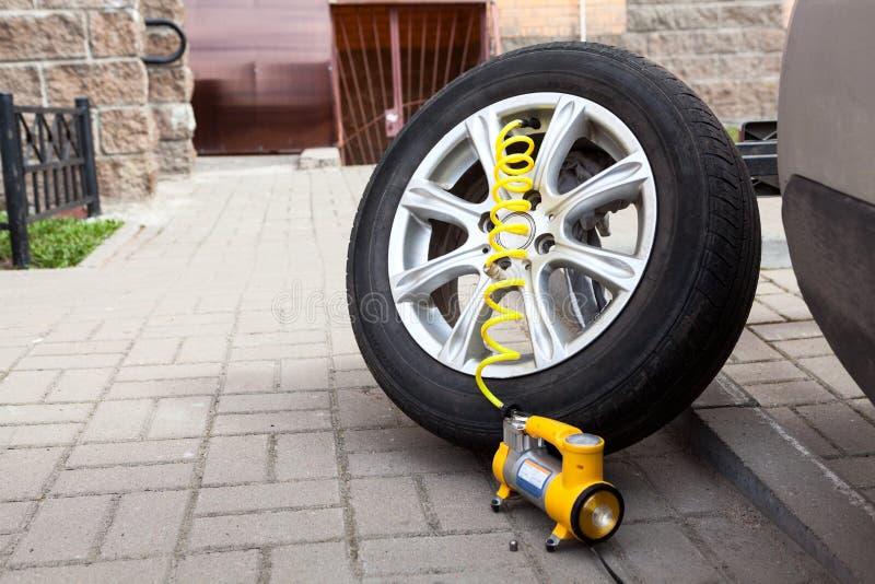 La rueda de coche desmontada lista para infla un neumático con la bomba neumática, copyspace fotos de archivo libres de regalías
