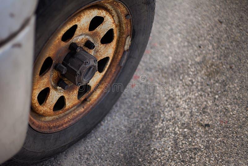La rueda vieja oxidada del camión parqueó en área al azar El negro oxidado coloreó el neumático determinado de la resma No tan pi fotos de archivo