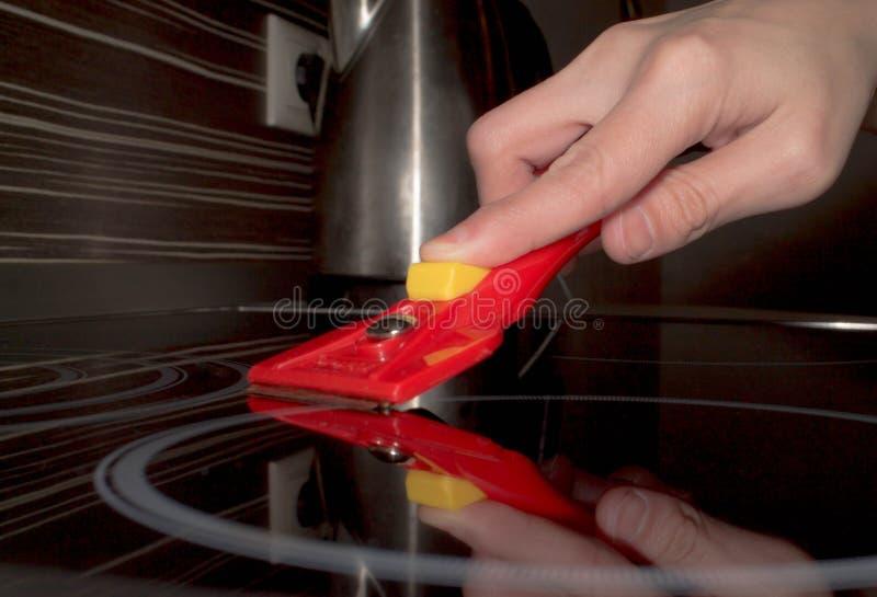 La ruspa spianatrice per vetro-ceramico nella mano elimina la fine della fresa fotografia stock