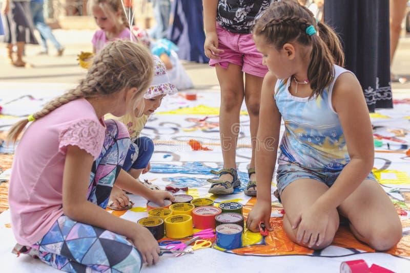 La RUSSIA, Krasnojarsk - 25 agosto: Bambine con nastro adesivo appiccicoso variopinto su un grande rotolo dell'insegna di plastic immagini stock