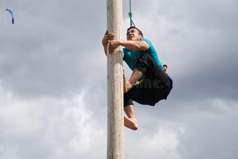 La Russia, Magnitogorsk, - 15 giugno, 2019 Un giovane scala su un palo di legno per i regali durante il Sabantuy - la festa nazio immagine stock