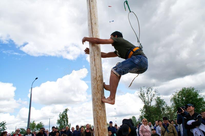 La Russia, Magnitogorsk, - 15 giugno, 2019 Un uomo scala un regalo su un alto palo di legno durante il Sabantuy - la festa nazion fotografia stock