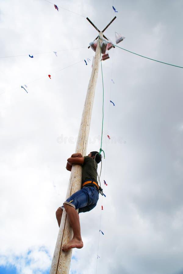 La Russia, Magnitogorsk, - 15 giugno, 2019 Un uomo scala su un palo di legno alto per un regalo durante il Sabantuy - la festa na fotografie stock libere da diritti