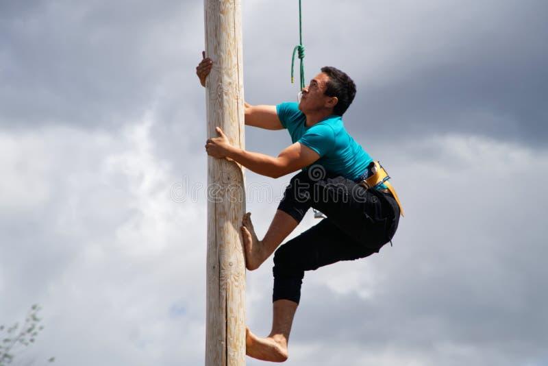 La Russia, Magnitogorsk, - 15 giugno, 2019 Un uomo scala su un palo di legno durante il Sabantuy - la festa nazionale dell'aratro immagini stock libere da diritti