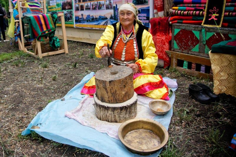 La Russia, Magnitogorsk, - 15 giugno, 2019 Una donna anziana dimostra il lavoro di vecchia mola manuale durante il Sabantui immagine stock libera da diritti