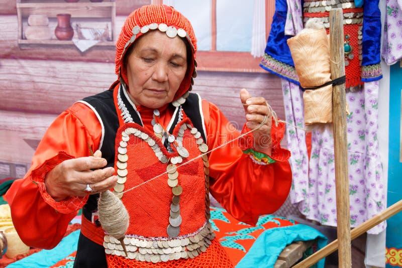 La Russia, Magnitogorsk, - 15 giugno, 2019 Una donna con un filato di rotazioni del fuso durante la festa Sabantuy Vestito nazion immagini stock libere da diritti
