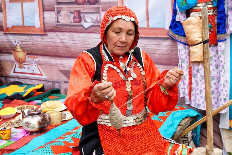 La Russia, Magnitogorsk, - 15 giugno, 2019 Una donna con un fuso dimostra il lavoro di una ruota di filatura manuale durante la f immagine stock