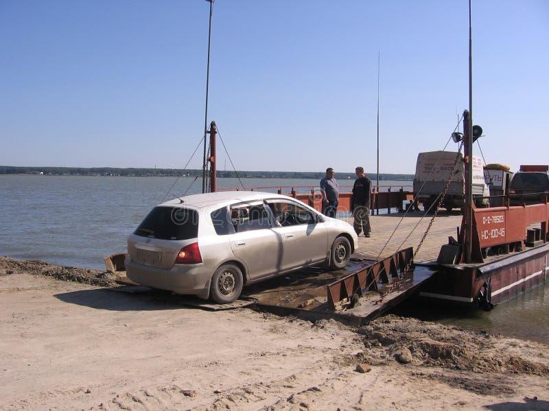 La Russia, Novosibirsk, il 15 luglio 2010: l'incrocio di traghetto sulle automobili del fiume chiama su una grande piattaforma di fotografia stock libera da diritti