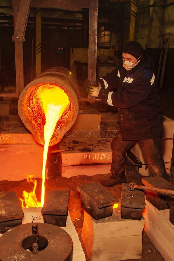 La Russia, Rjazan'14 febbraio 2019 - il lavoratore versa i resti di metallo fuso in fabbrica del processo della colata del metall immagini stock libere da diritti