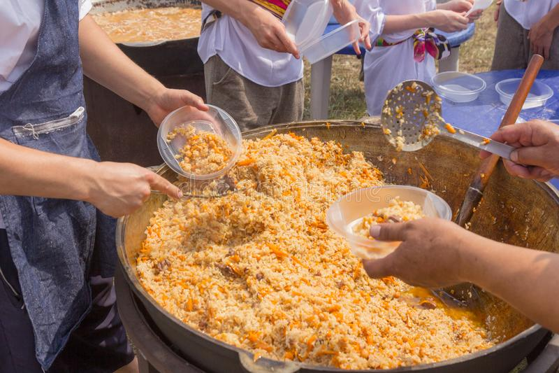 La Russia, samara, luglio 2018: Il cuoco dell'Uzbeco presenta il pilaf cucinato in piatti durante la festa festival Ethno-storico fotografia stock